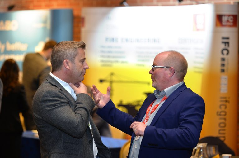 A speaker and an attendee converse over coffee Construction Frameworks Conference, Kensington Town Hall. 02.10.19