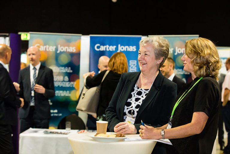 Carter Jonas Exhibition stand with Attendees talking at West Yorkshire Economic Growth Conference 2018